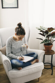 Woman sitting in armchair writing on notepad - EBSF001246