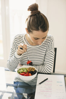 Woman sitting at table with fruit muesli looking at notepad - EBSF001249