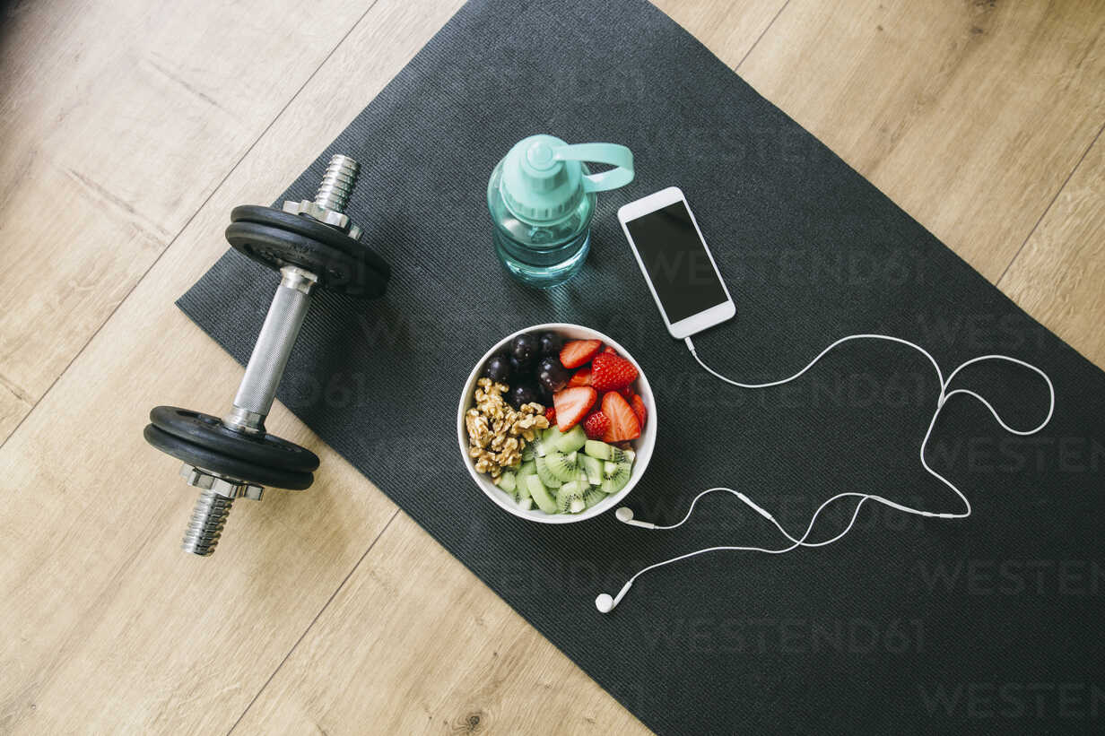 Dumbbell, drinking bottle, fruit bowl and smartphone with earphones - EBSF001258 - Bonninstudio/Westend61