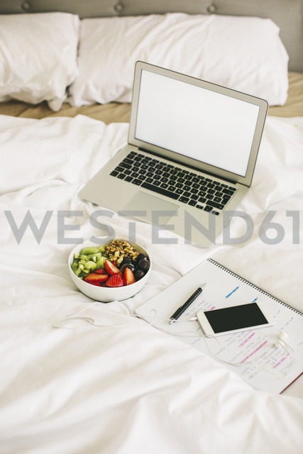 Laptop, notepad, fruit bowl and smartphone with earphones on blanket - EBSF001261 - Bonninstudio/Westend61