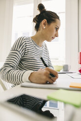 Woman at desk writing in notebook - EBSF001273