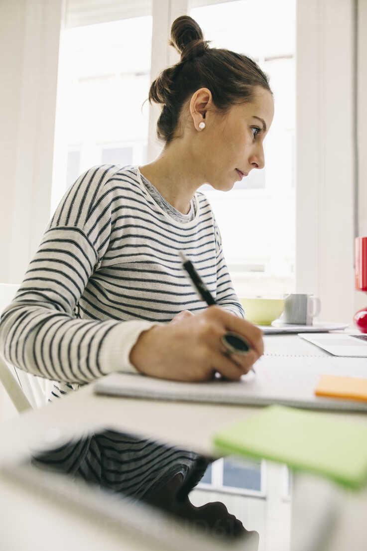 Woman at desk writing in notebook - EBSF001273 - Bonninstudio/Westend61