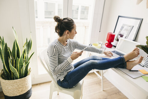 Woman at home laying feet on table using laptop - EBSF001279