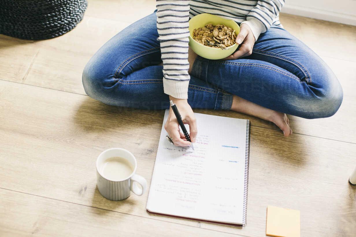 Woman sitting on floor with muesli bowl writing on notepad - EBSF001285 - Bonninstudio/Westend61