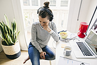 Woman at home sitting at table wearing headphones - EBSF001288