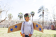 Portrait of happy little boy dressed up as a superhero standing on a meadow - VABF000354