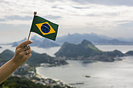 Brazil, woman holding Brazilian flag on a viewpoint in Rio de Janeiro - MAUF000325