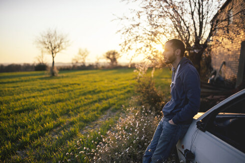 Man leaning against a car looking at a green field at sunset - GEMF000785
