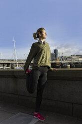 UK, London, female runner stretching at riverwalk - BOYF000129
