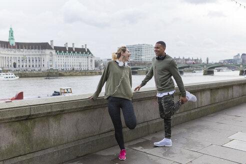 UK, London, two happy runners stretching at riverwalk - BOYF000138