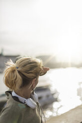 UK, London, woman with headphones at riverwalk in backlight - BOYF000150