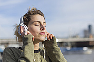 UK, London, woman listening music at River Thames - BOYF000153