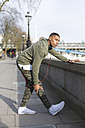 UK, London, runner stretching at riverwalk - BOYF000156