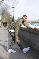 UK, London, runner stretching at riverwalk - BOYF000156