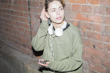 Young woman with headphones and smartphone at brick wall at night - BOYF000162