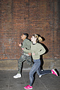 UK, London, man and woman running at night along brick wall - BOYF000165