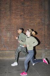UK, London, man and woman running at night along brick wall - BOYF000165