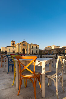Sicily, Marzamemi, tables and chairs of restauraunt, chapel in the background - CSTF001017