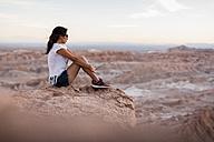 Chile, San Pedro de Atacama, woman sitting on rock in the Atacama desert - MAUF000346