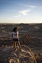 Chile, San Pedro de Atacama, woman standing on rock in the Atacama desert - MAUF000367