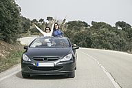 Women having fun in a convertible car on a country road - ABZF000277