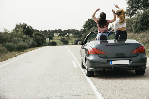 Women having fun in a convertible car on a country road - ABZF000280