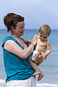Mother creaming her baby with suncream on the beach - DSF000642