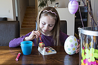 Smiling girl painting Easter egg at home - SARF002626