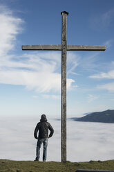 Germany, Bavaria, man standing next to summit cross on Blomberg at atmospheric inversion - CRF002745