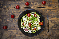 Bowl of zucchini spaghetti with mozzarella, cherry tomatoes and basil on wood - LVF004639