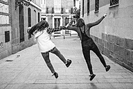 Spain, Madrid, back view of two young women jumping in a street - ABZF000287