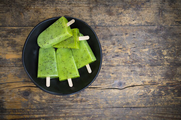 Bowl of homemade kiwi ice lollies on dark wood - LVF004645