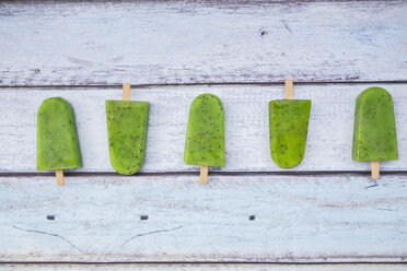 Row of homemade kiwi ice lollies on  wood - LVF004648