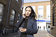 Young woman with cell phone on urban street - BOYF000178