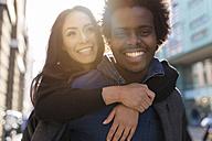 Happy young man carrying girlfriend piggyback - BOYF000205