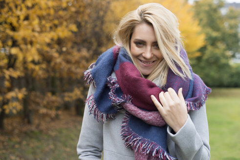 Portrait of happy young woman wearing fashionable shawl in autumnal park - LFOF000190