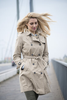 Portrait of young woman wearing trench coat walking on a bridge - LFOF000193