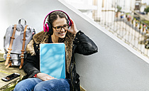 London, student girl with headphone and writing pad, language holiday - MGOF001523