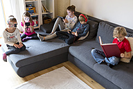 Four children on a couch using different digital devices while one boy reading a book - SARF002644