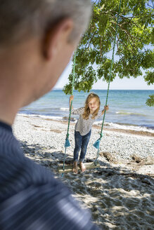 Smiling girl standing on a swing on the beach looking at her father in the foreground - OJF000125