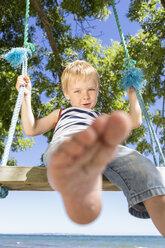 Portrait of blond boy sitting on a swing - OJF000128