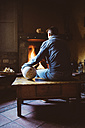 Man sitting in front of the fireplace with a soccer ball - GEMF000790