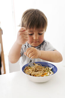 Little boy eating veggie pasta with a fork - VABF000356