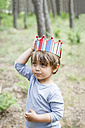 Portrait of little boy with wood stick wearing paper crown in the woods - VABF000359