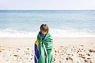 Little boy wrapped in Brazilian flag on a beach - VABF000365