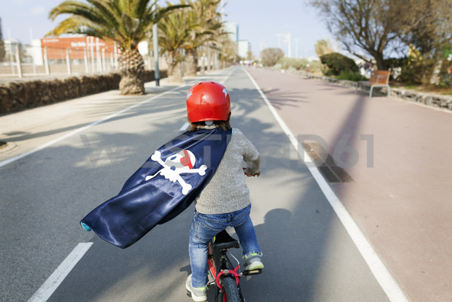 Spain, Barcelona, back view of little boy with a pirate cape riding bicycle on an empty street - VABF000368 - Valentina Barreto/Westend61