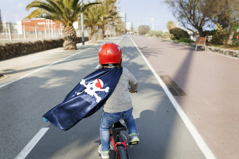 Spain, Barcelona, back view of little boy with a pirate cape riding bicycle on an empty street - VABF000368