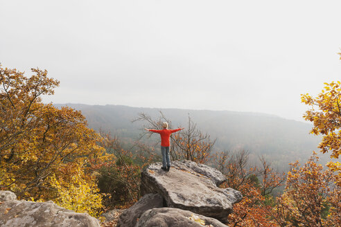 Germany, Rhineland Palatinate, Palatinate Forest, woman practising yoga on Drachenfels in autumn - GWF004645