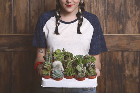 Hipster young woman with tray cacti and succulents - RTBF000006