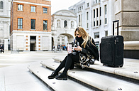 UK, London, young woman with luggage checking her cell phone on stairs - MGOF001530